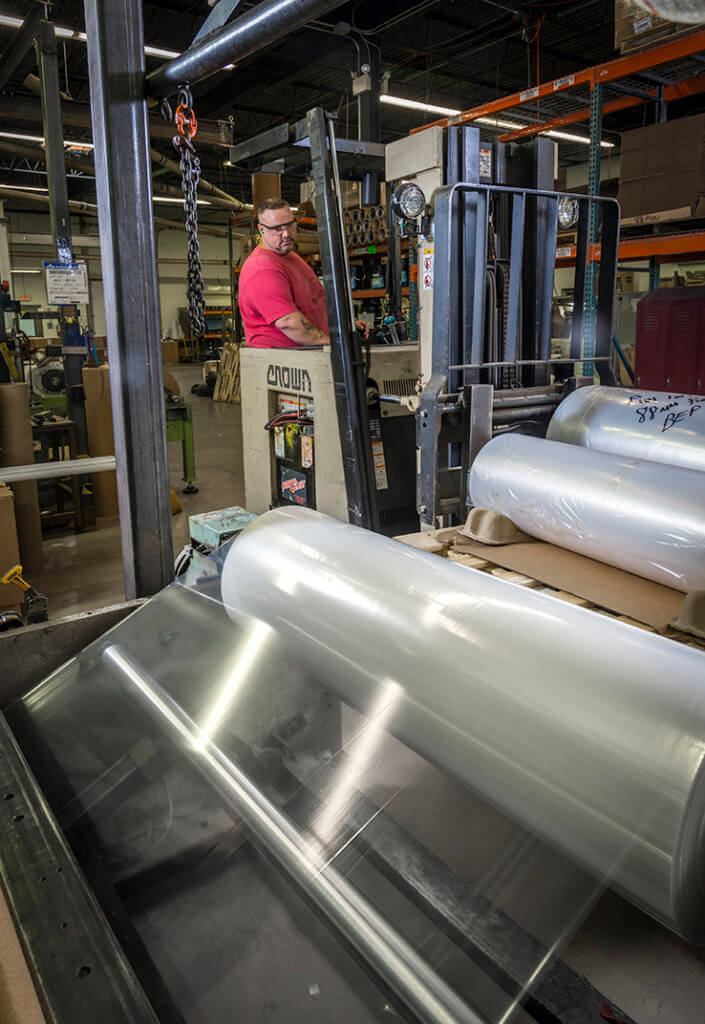 Tagline employee operates forklift to lift a roll of thin LDPE film